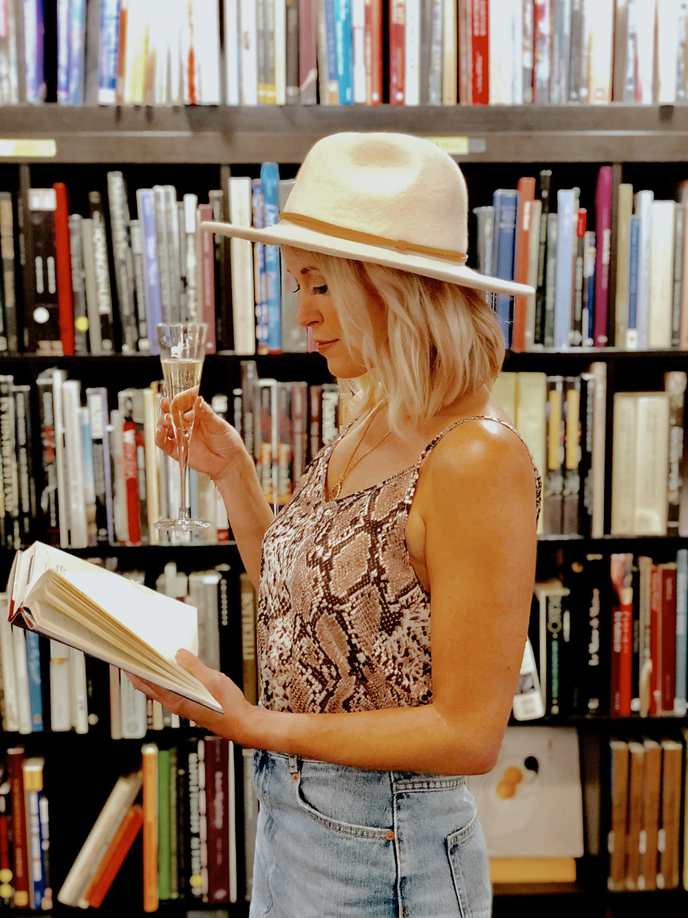 Woman reads a book and holds a flute of champagne at the Battery Park Book Exchange and Champagne Bar at the Grove Arcade in Asheville North Carolina. Local travel guide and lifestyle blogger The Tony Townie.