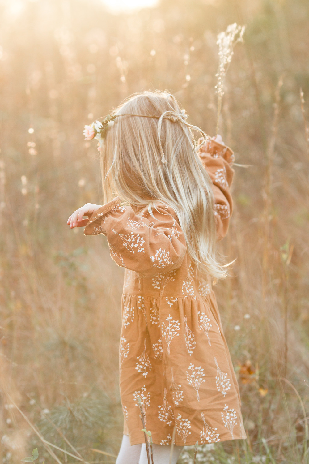 Rear view of little girl dancing in a grassy field wearing a flower crown, London Adelaide family photography, Asheville family photographers, tips for planning family photos, lifestyle blog