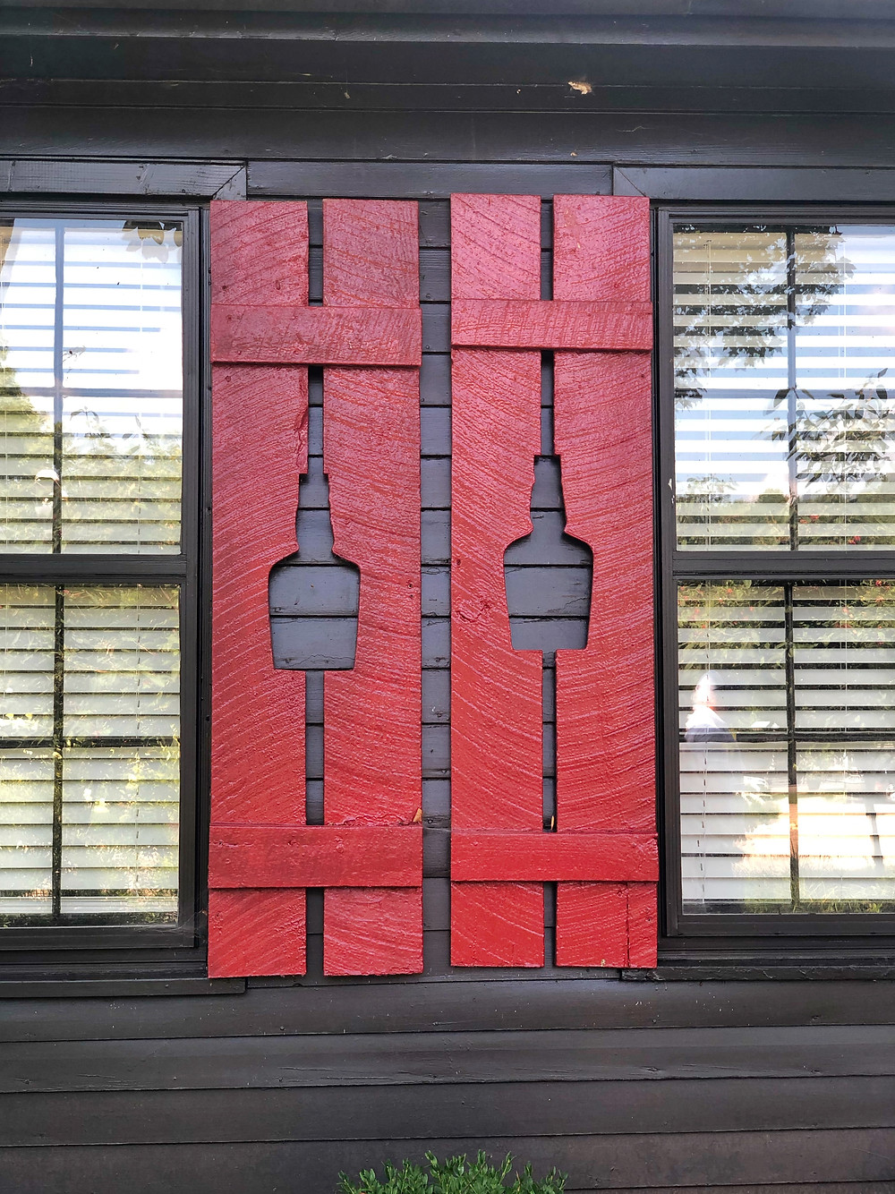 Red shutters with bourbon bottle cut outs at Maker's Mark distillery, Bourbon Trail travel guide, travel blog, best distillery tour