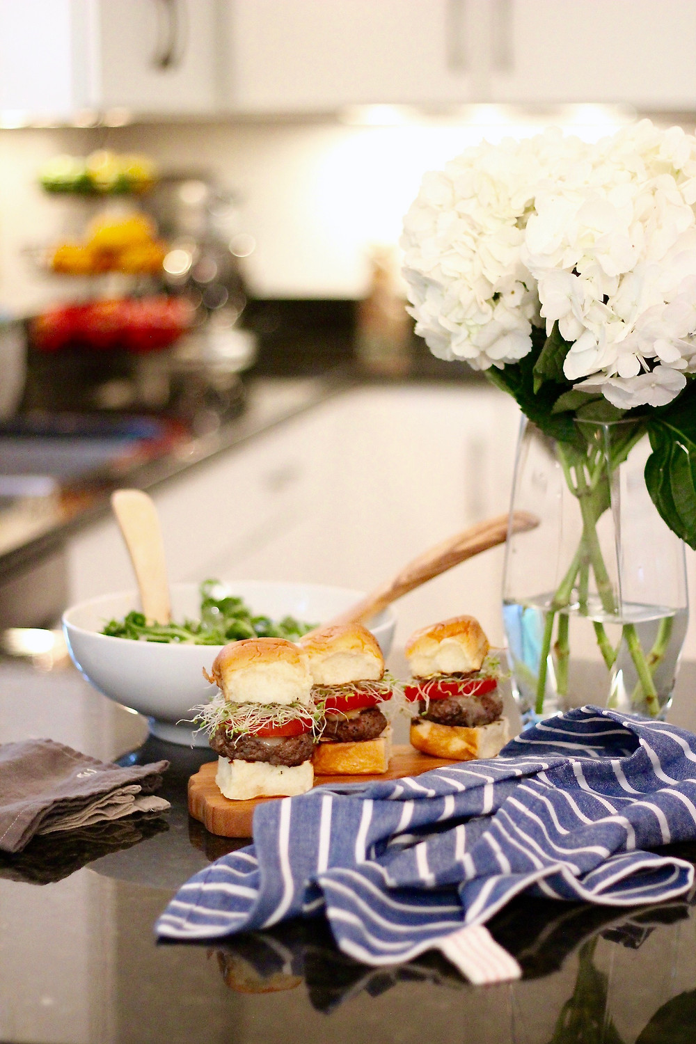 Hydrangeas sit next to a summer spread of burgers and watermelon salad