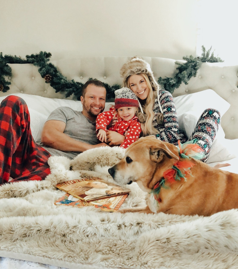 Family snuggles in bed wearing coordinating Christmas pajamas.