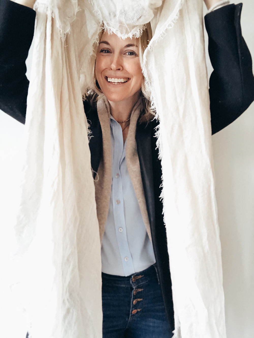 Woman peaks through middle of gauzy ivory scarf.