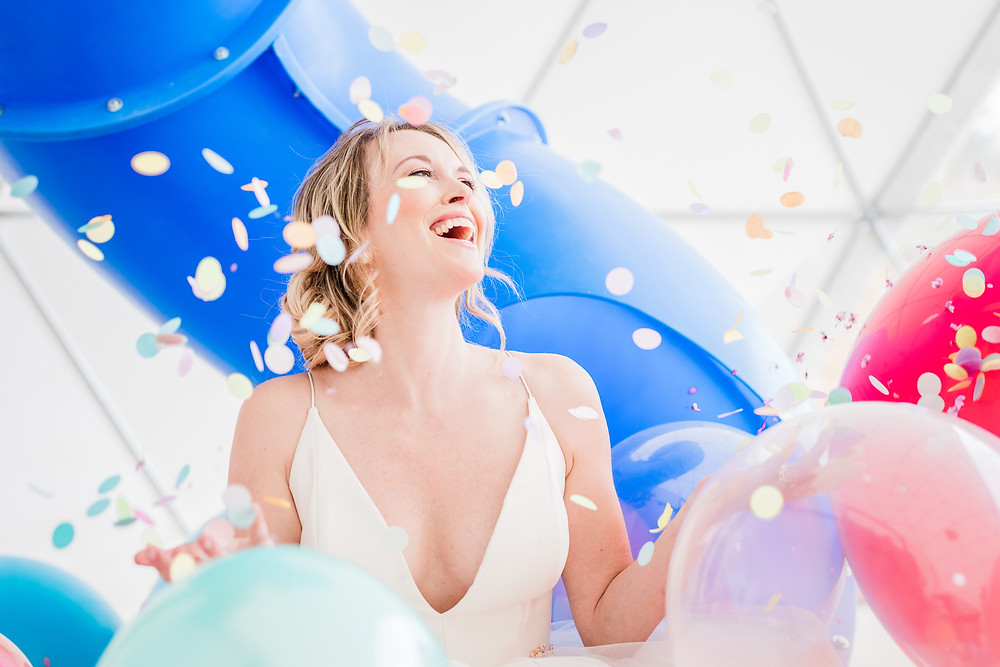 Bride laughs as round pastel confetti falls around her