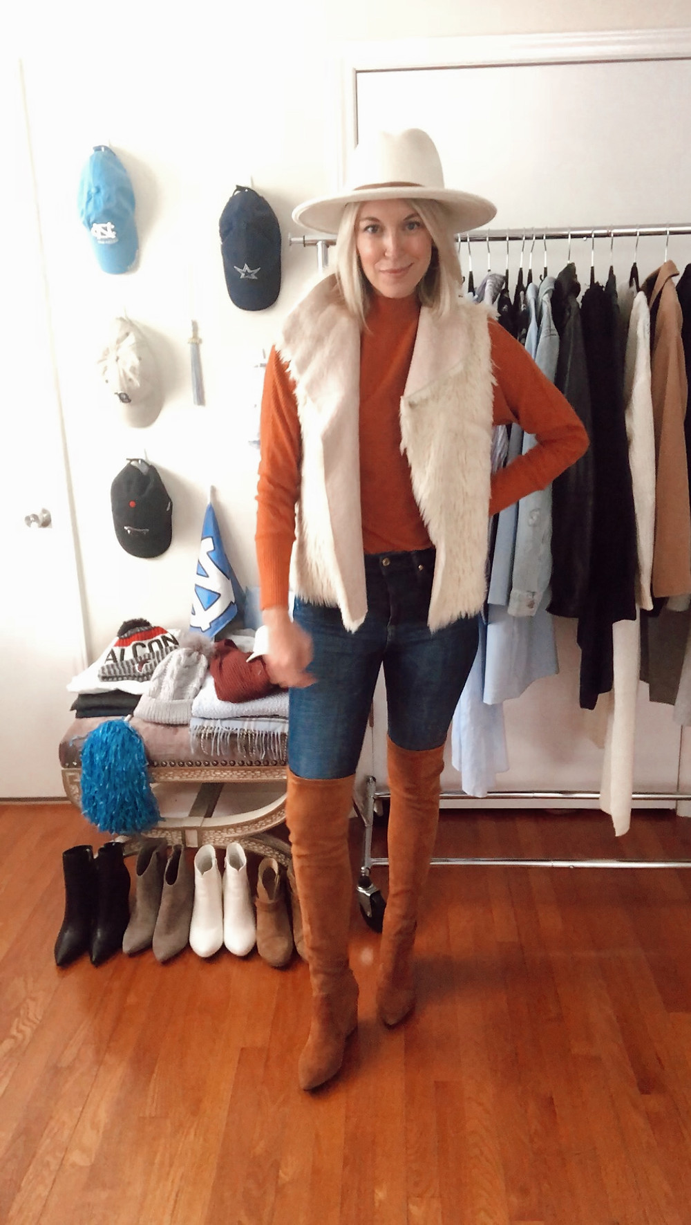 Game day outfit idea for Clemson and Tennessee football fans: orange sweater, white faux fur vest, jeans, over the knee boots. Fashion blogger and wardrobe stylist.