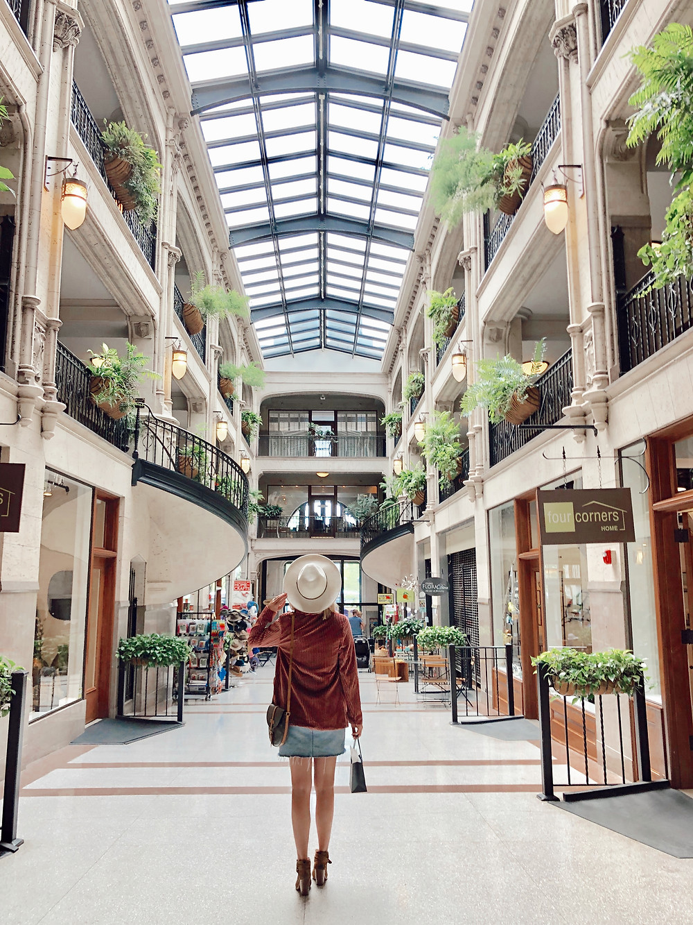 Woman looks down skylit atrium in the Grove Arcade in Asheville North Carolina. Local travel guide and lifestyle blogger The Tony Townie.