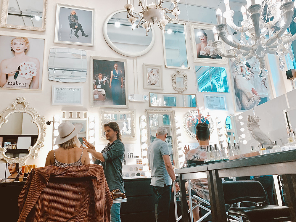Framed photos, mirrors, and chandeliers line the walls of Serenity + Scott Apothecary in the Grove Arcade in Asheville North Carolina. Local travel guide and lifestyle blogger The Tony Townie.