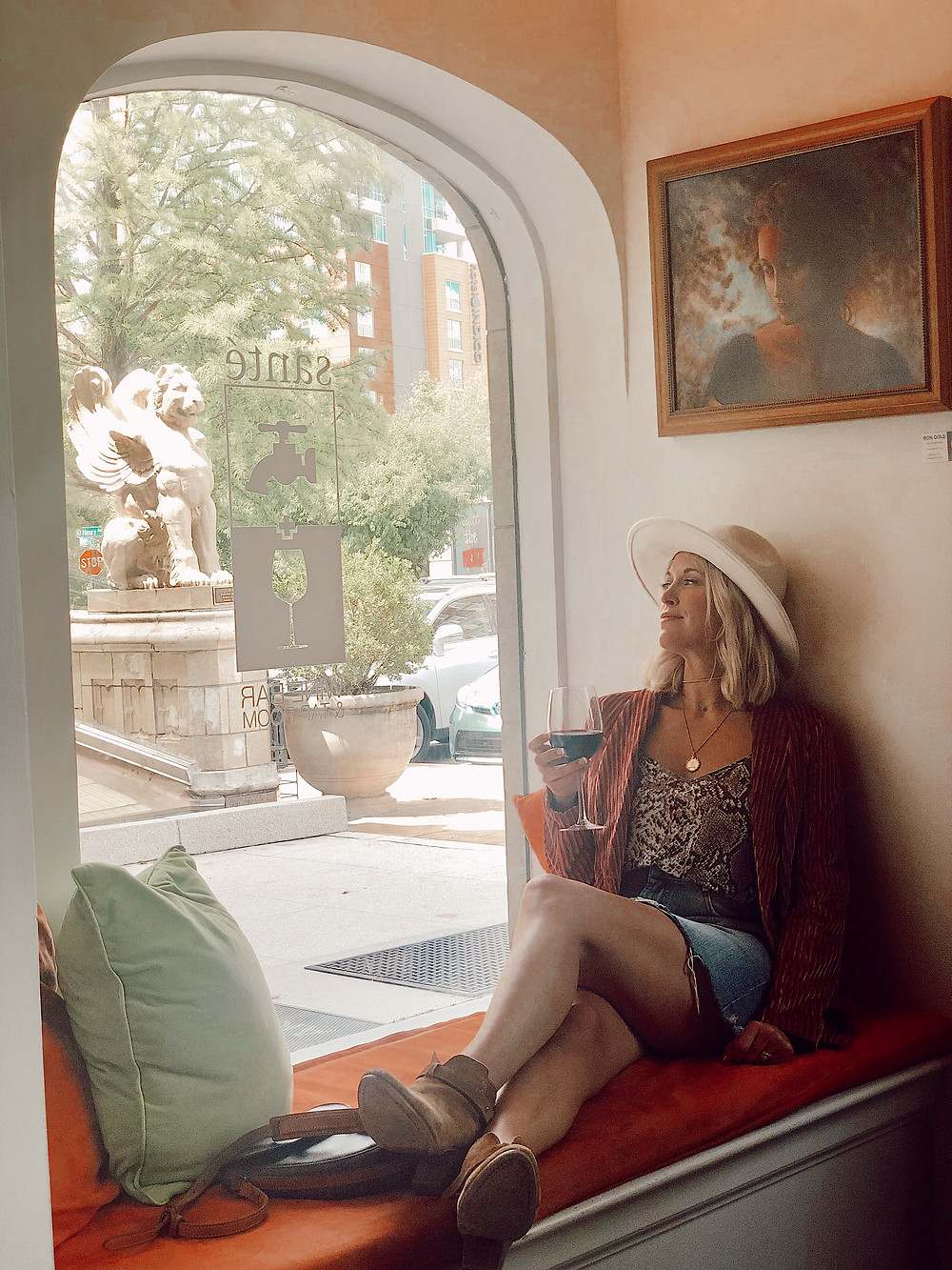 Woman sits in window seat holding a glass of red wine at Santé Wine Bar and Tap Room in the Grove Arcade in Asheville North Carolina. Local travel guide and lifestyle blogger The Tony Townie.