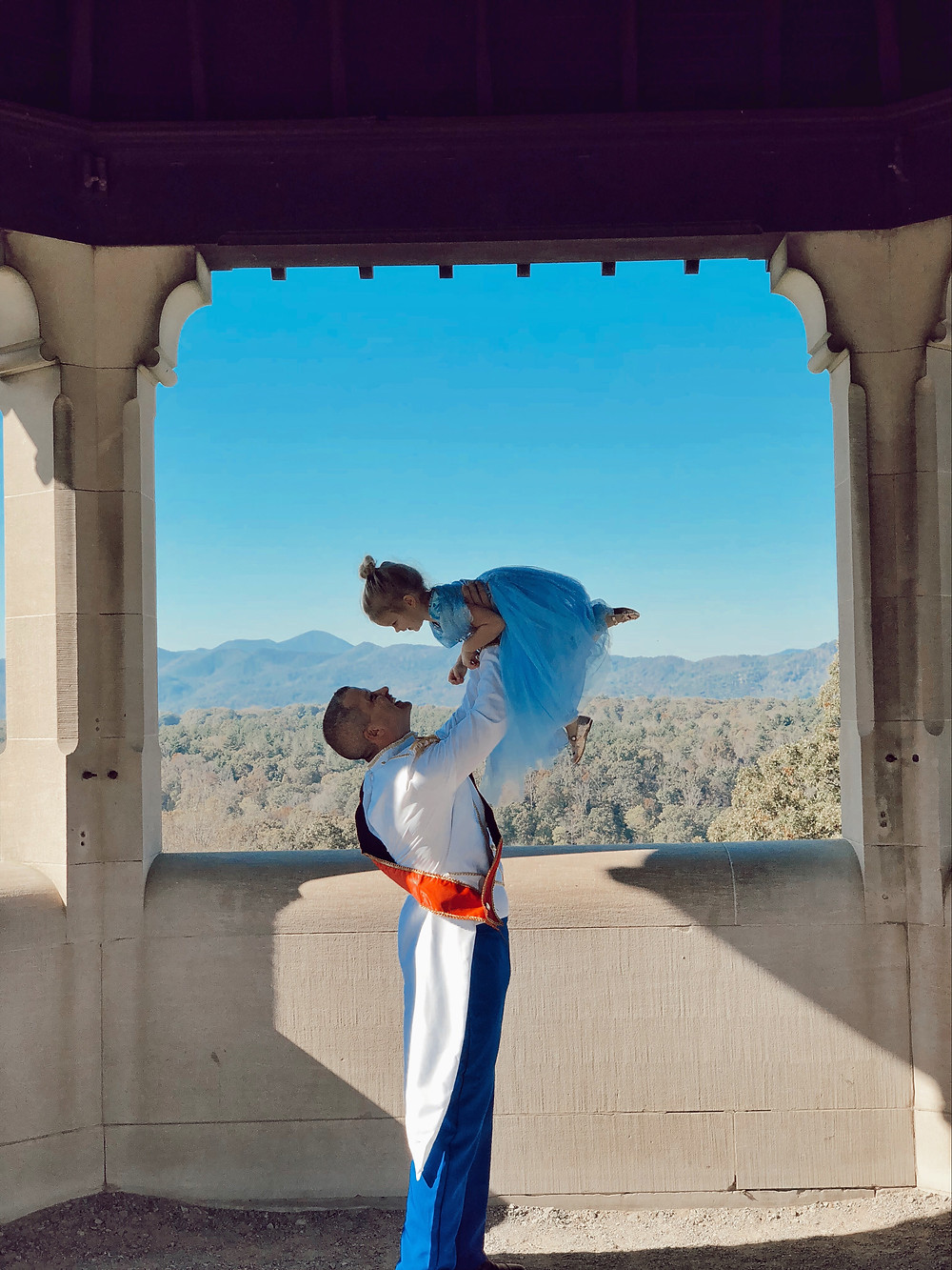 A dad dressed as Prince Charming lifts his daughter in her Cinderella dress up in the air.