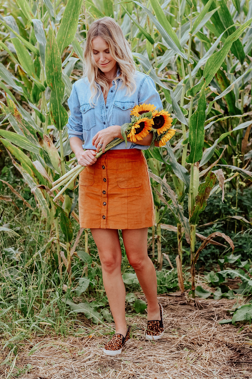 Brooke (The Tony Townie) wearing chambray blouse and corduroy skirt walks through corn field holding sunflowers.
