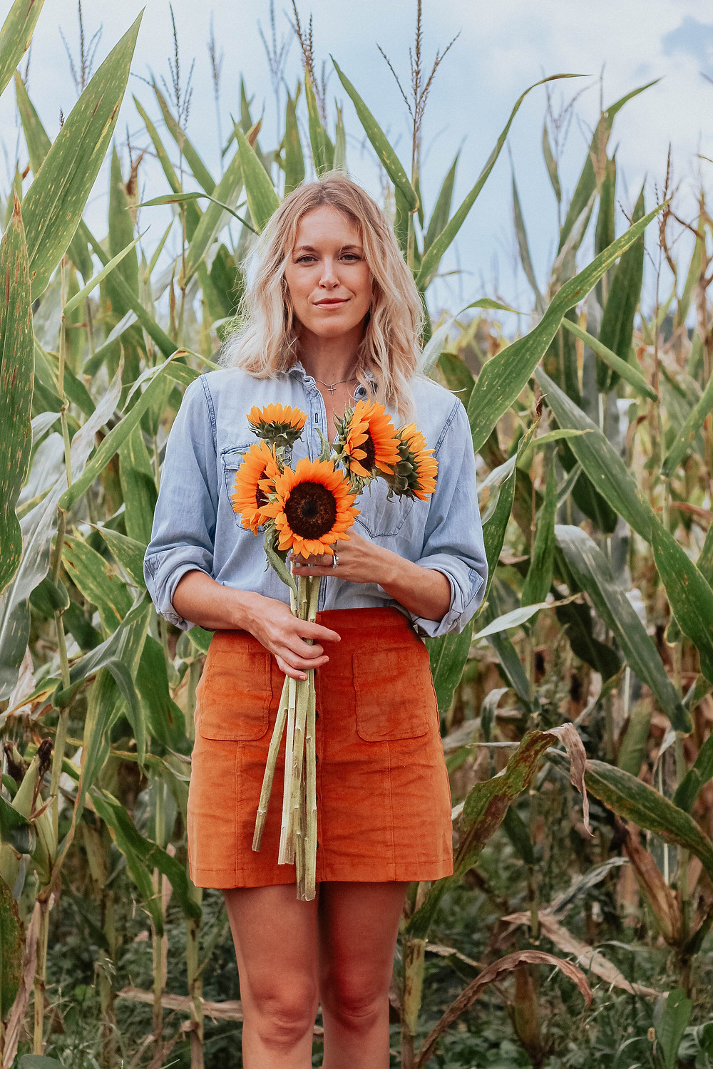 Brooke (The Tony Townie) wearing chambray blouse and corduroy skirt holds sunflowers.