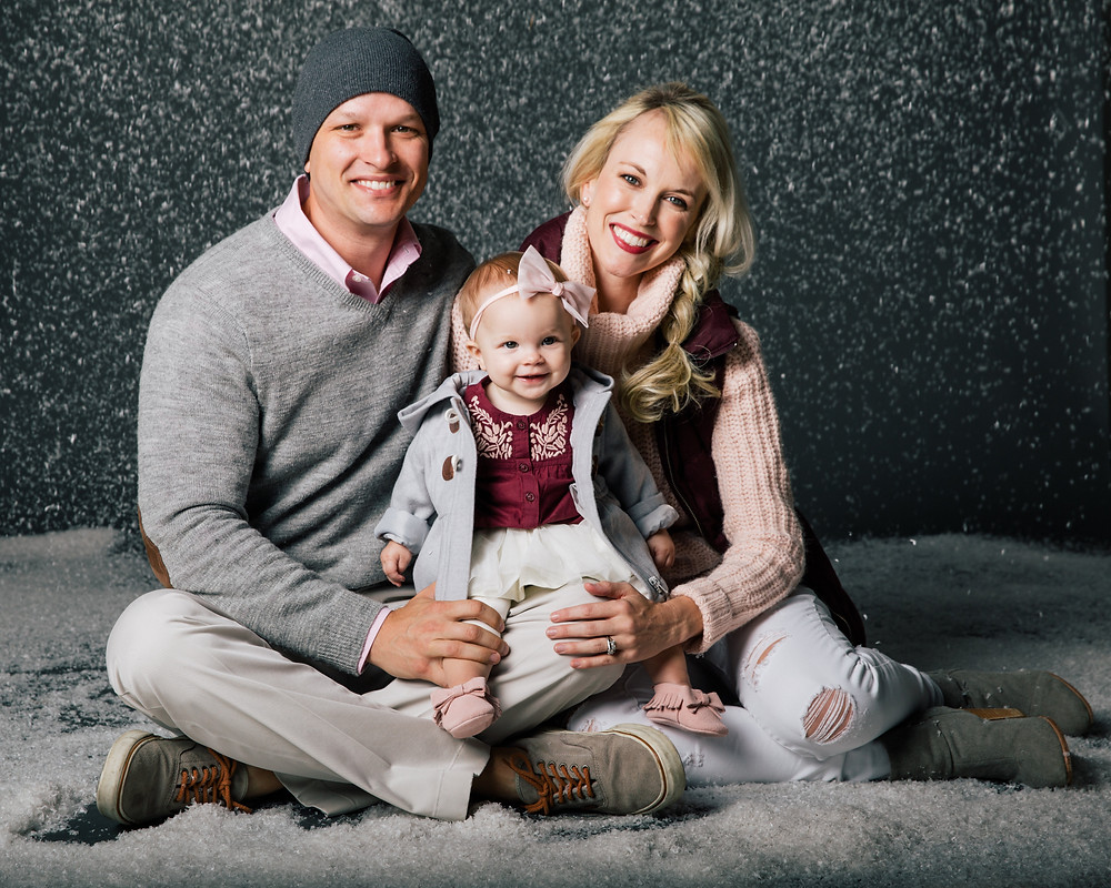 Family poses for their Christmas Card photo in a studio with fake snow falling around them.