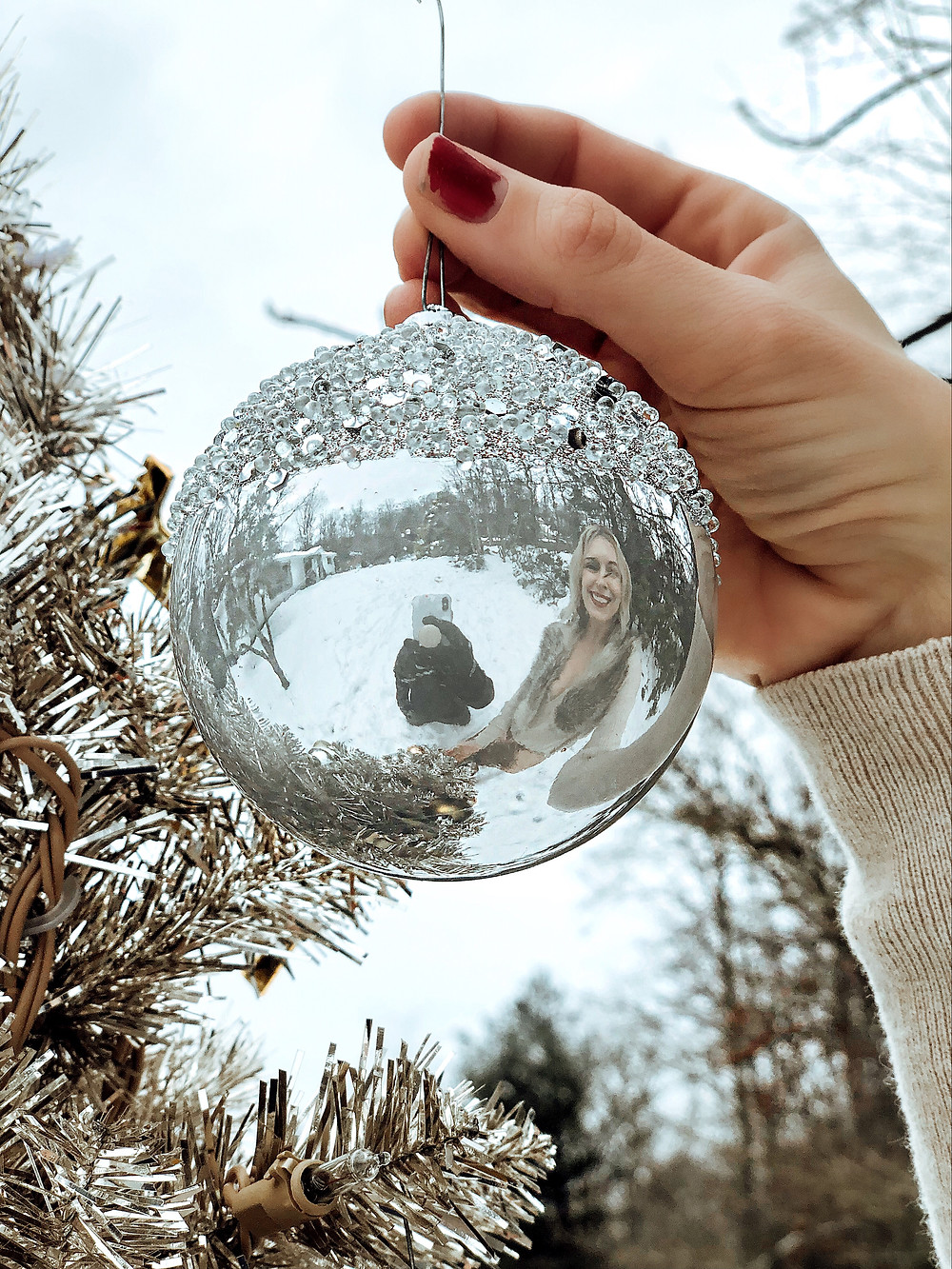 Husband takes photo of him and his wife in the reflection of a silver Christmas ornament.