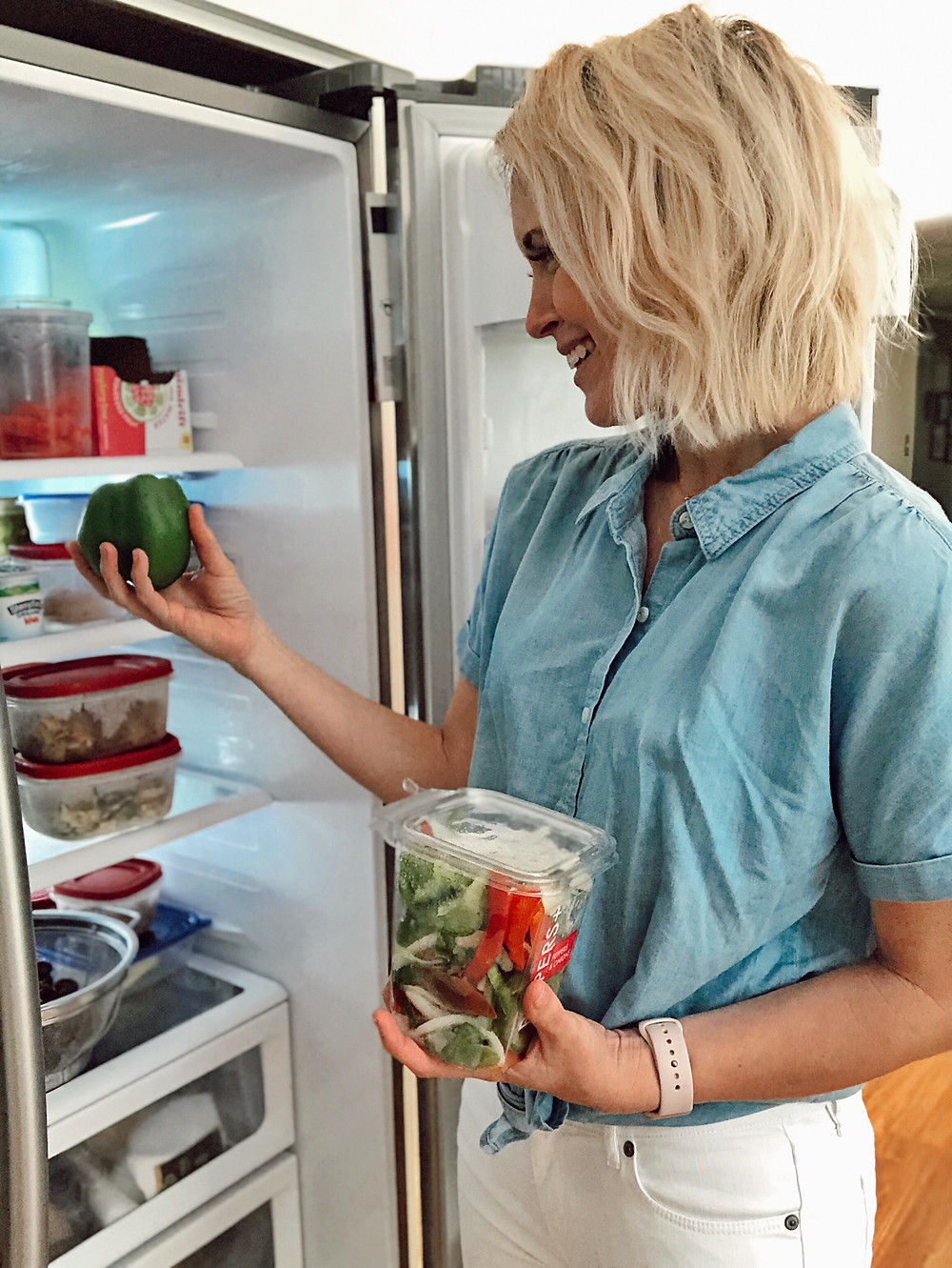 woman wearing chambray blouse pulls fresh vegetables out of her refrigerator
