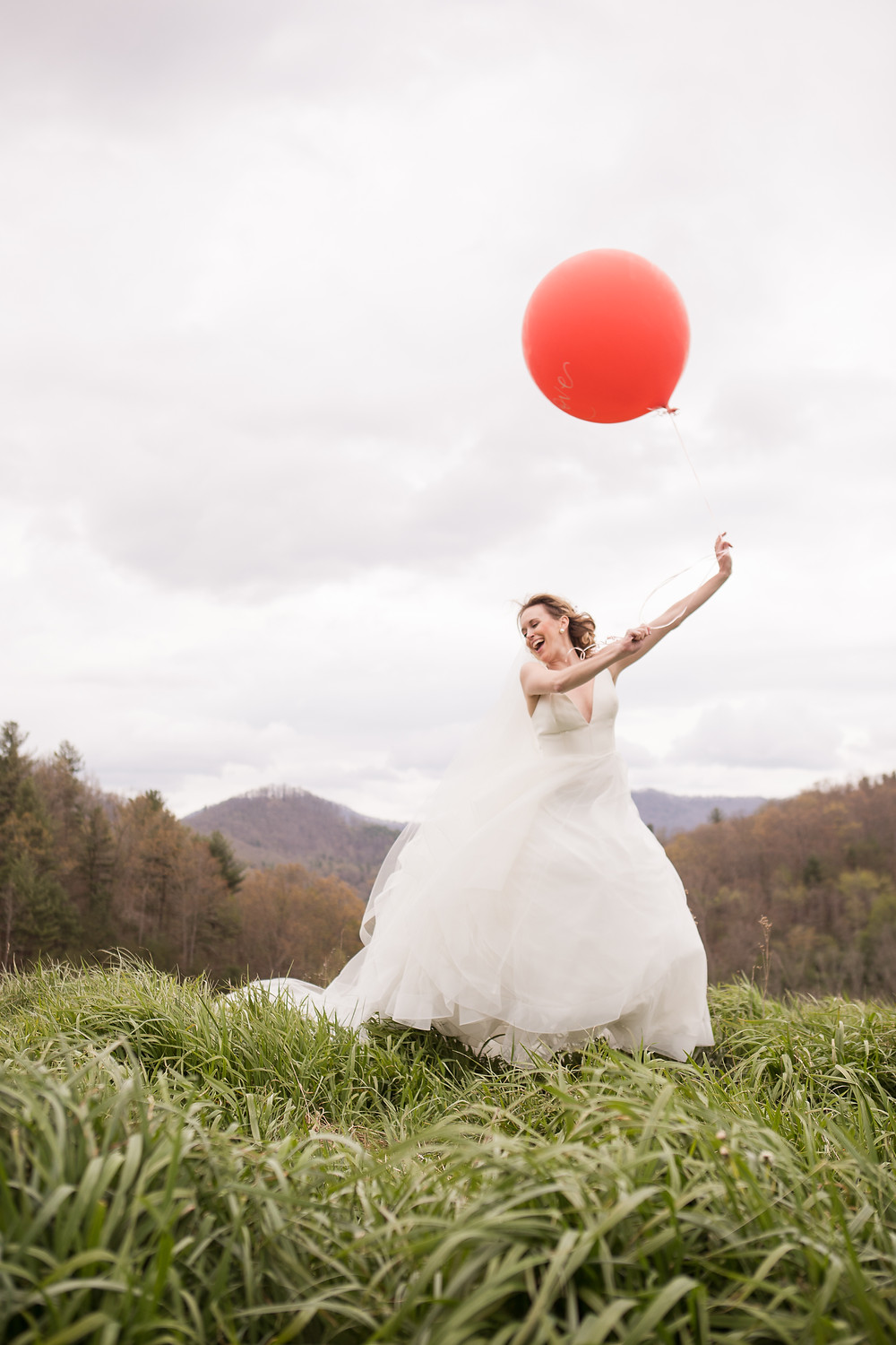 Bride running in a mountain meadow with a round red balloon