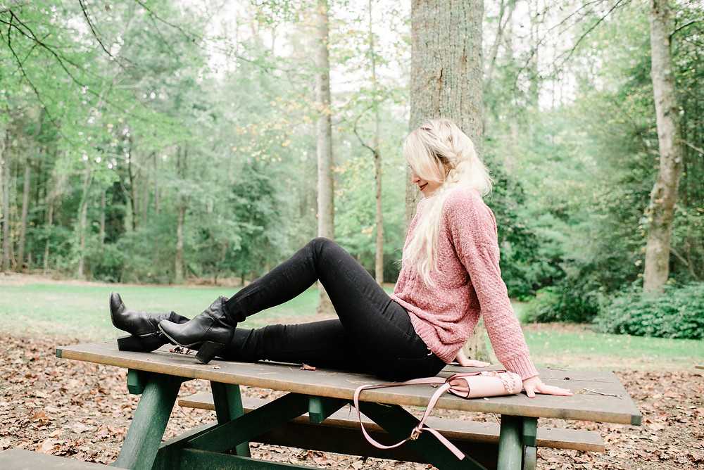 Brooke Williams sits on top of picnic table wearing pink chenille sweater, black jeans, and black boots