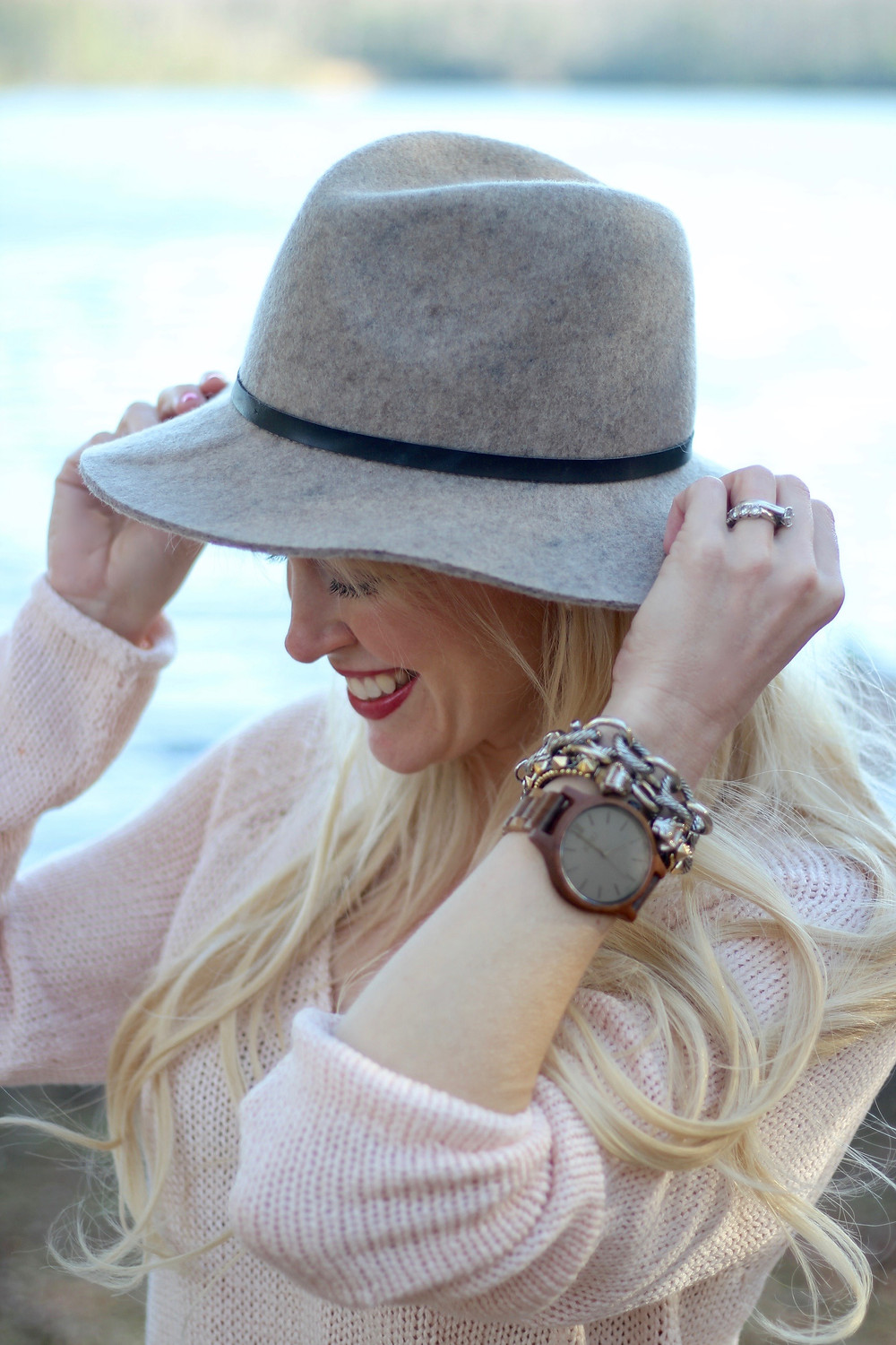 A happy young mom clutches her wide brim hat and shows her JORD Wood Watch.