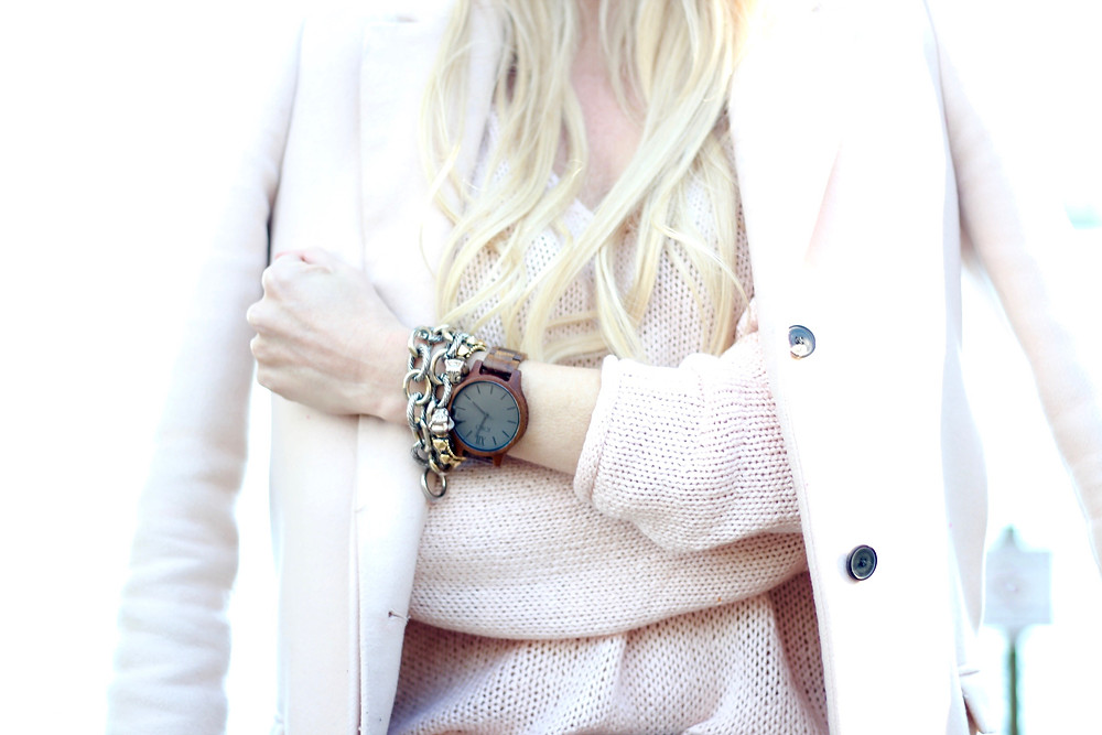 Layers of blush pink winter styles frame the wrist of a young mom wearing her JORD Wood Watch.