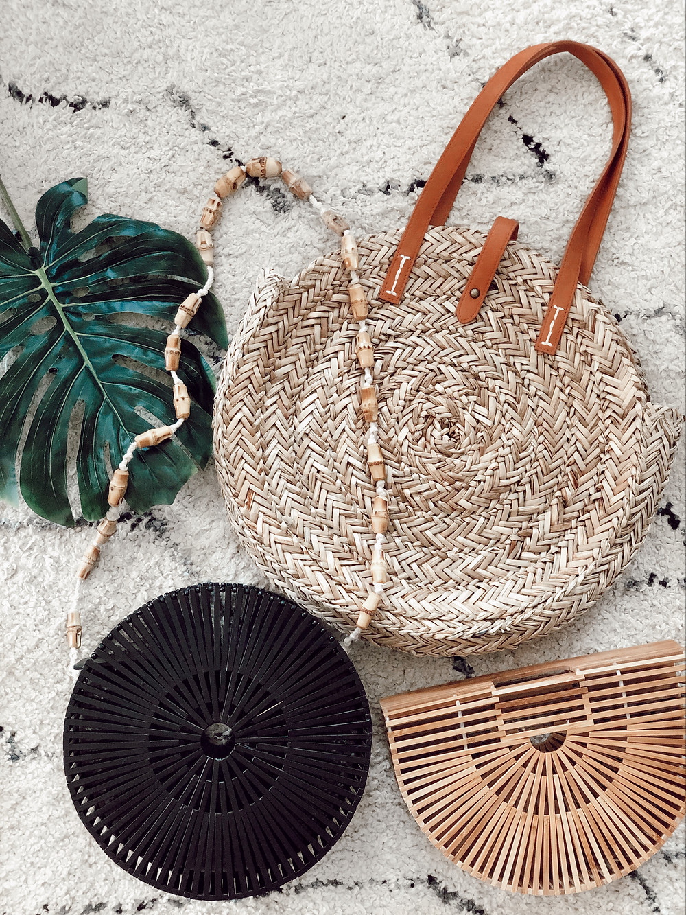 Round straw tote, round black wooden bag, and wooden ark bag lie on white rug