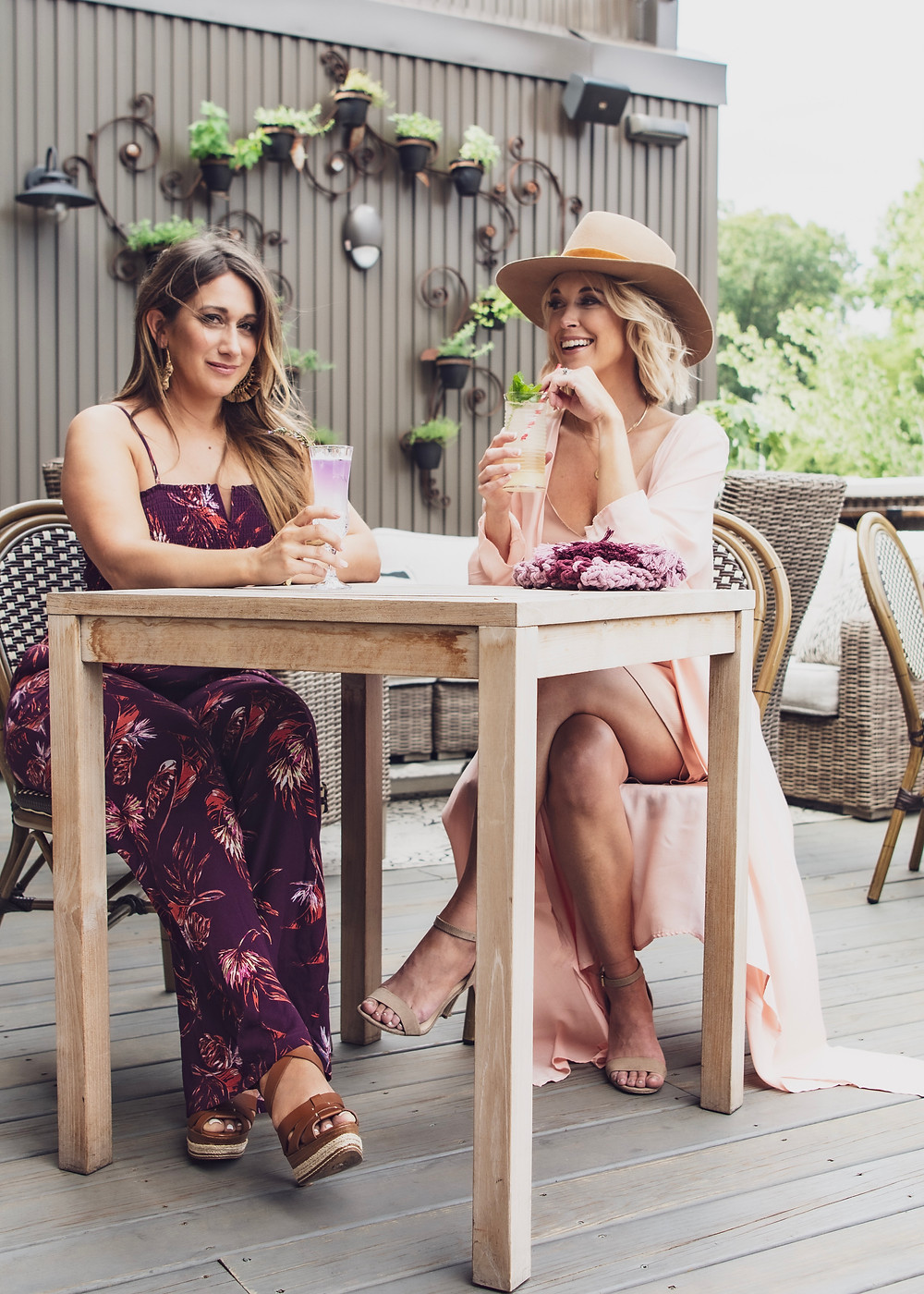 Two local lifestyle bloggers share hand-crafted cocktails on the rooftop of Antidote Bar in downtown Asheville wear clothes from Nest Boutique.