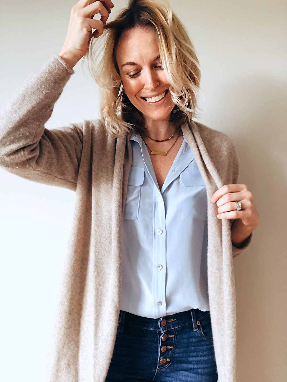 Light tan cashmere cardigan draped over pale blue blouse and button-front blue jeans.