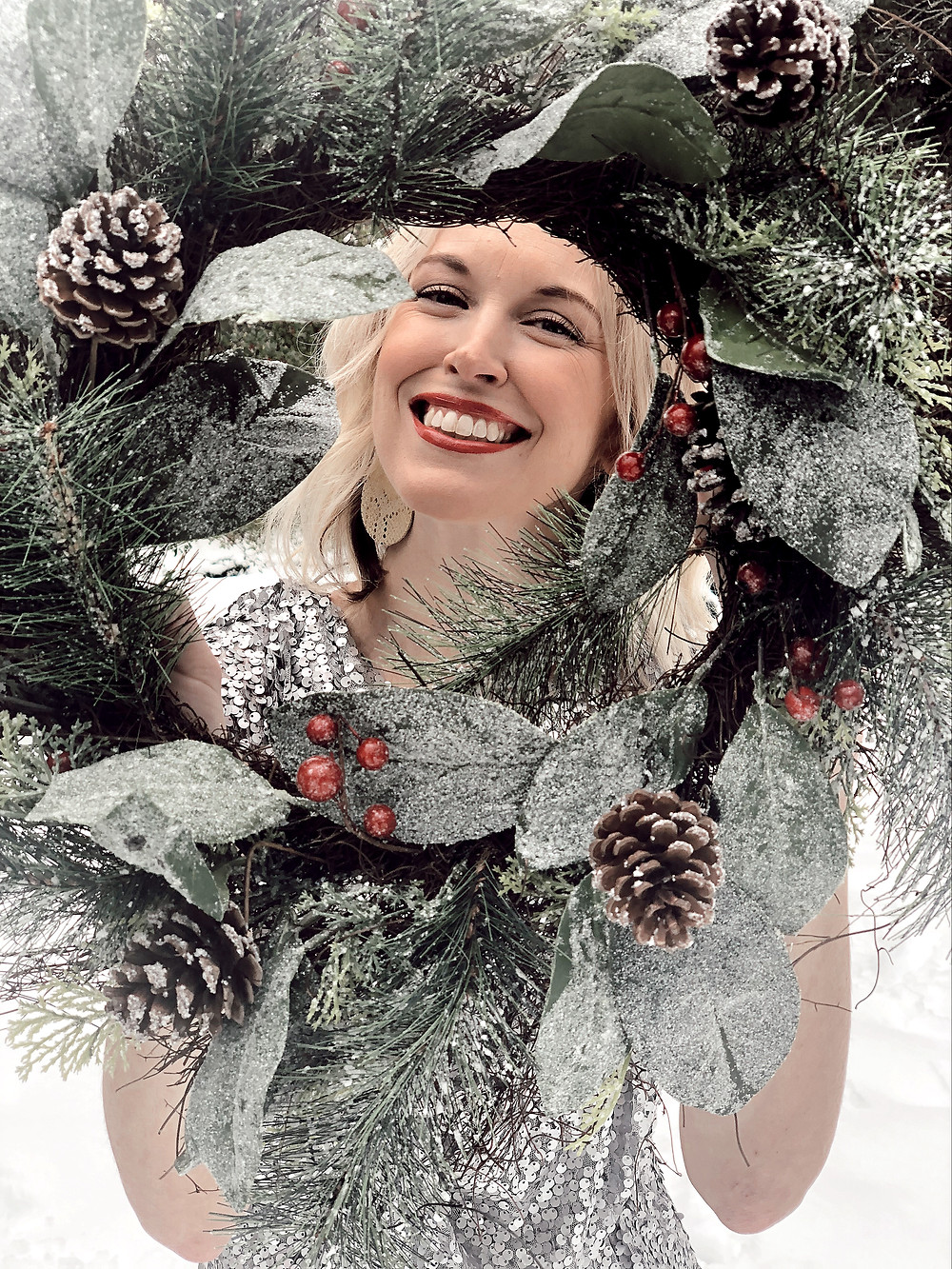 Woman wearing silver sequin dress and crystal bracelet smiles through a pine cone wreath.