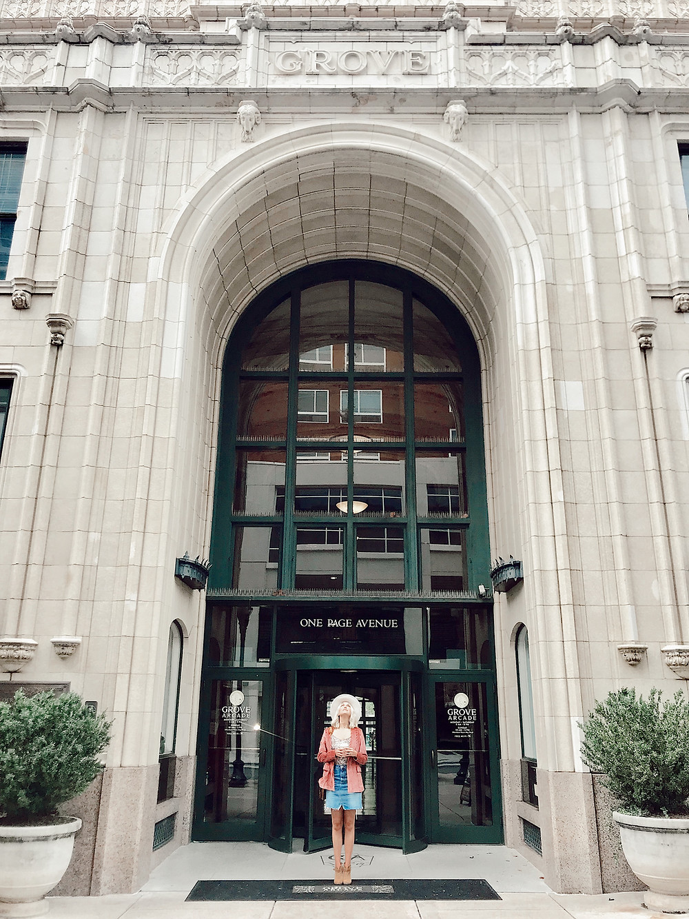 Woman stands outside tall arched revolving doorway into Grove Arcade in Asheville North Carolina. Local travel guide and lifestyle blogger The Tony Townie.