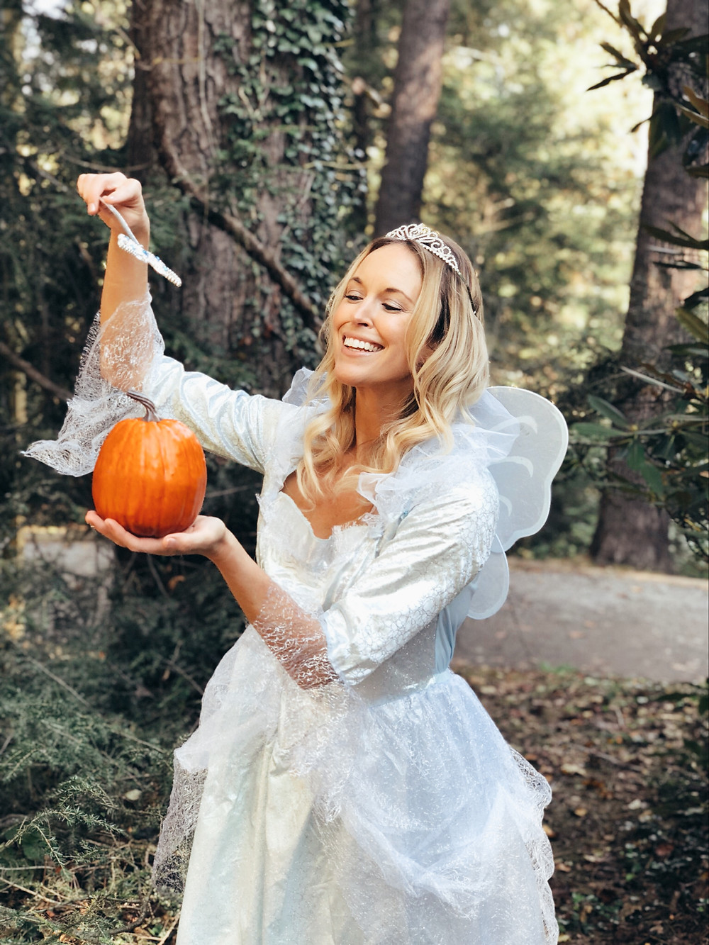 A woman dressed as the Fairy Godmother from Cinderella waves her magic wand at a pumpkin.