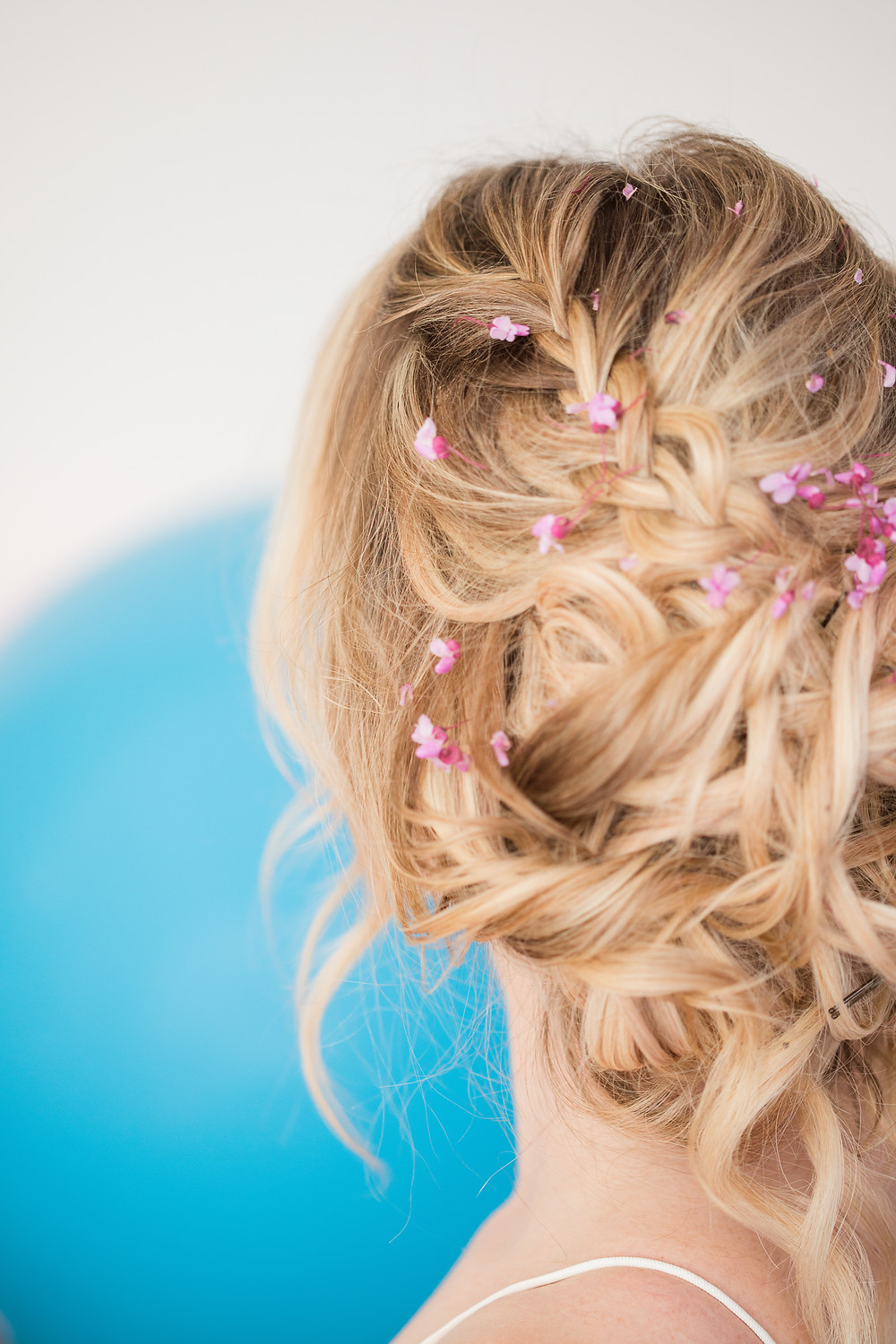 Tiny flowers sit atop a bridal braided wedding updo