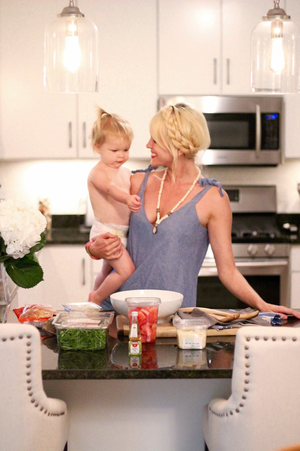 Mom Brooke Wiliams hold daughter Harlow as they cook together in their kitchen