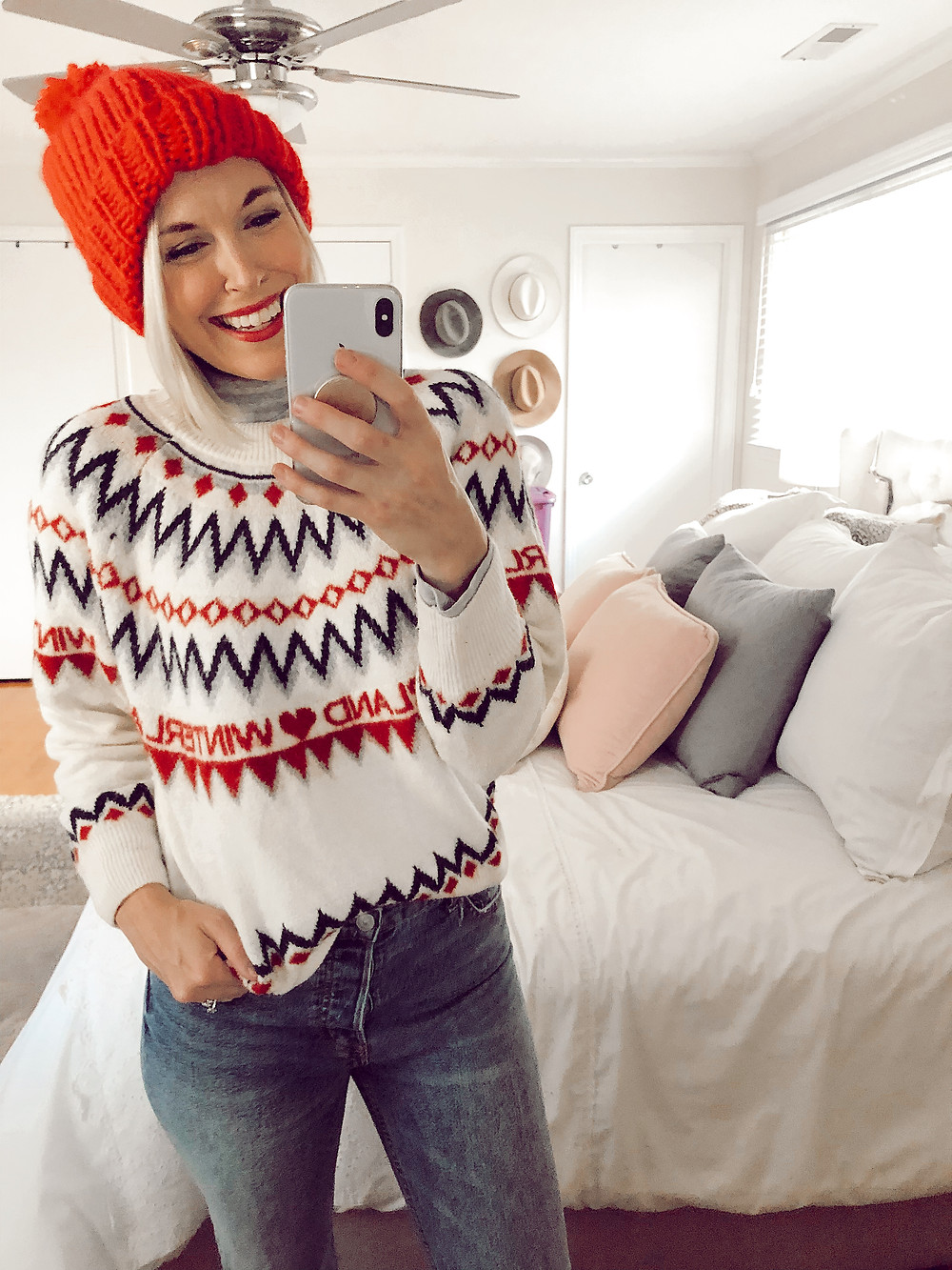 Outfit selfie in H&M Christmas sweater layered over gray turtleneck and jeans with a red knit beanie, fashion blog, casual fall outfit ideas
