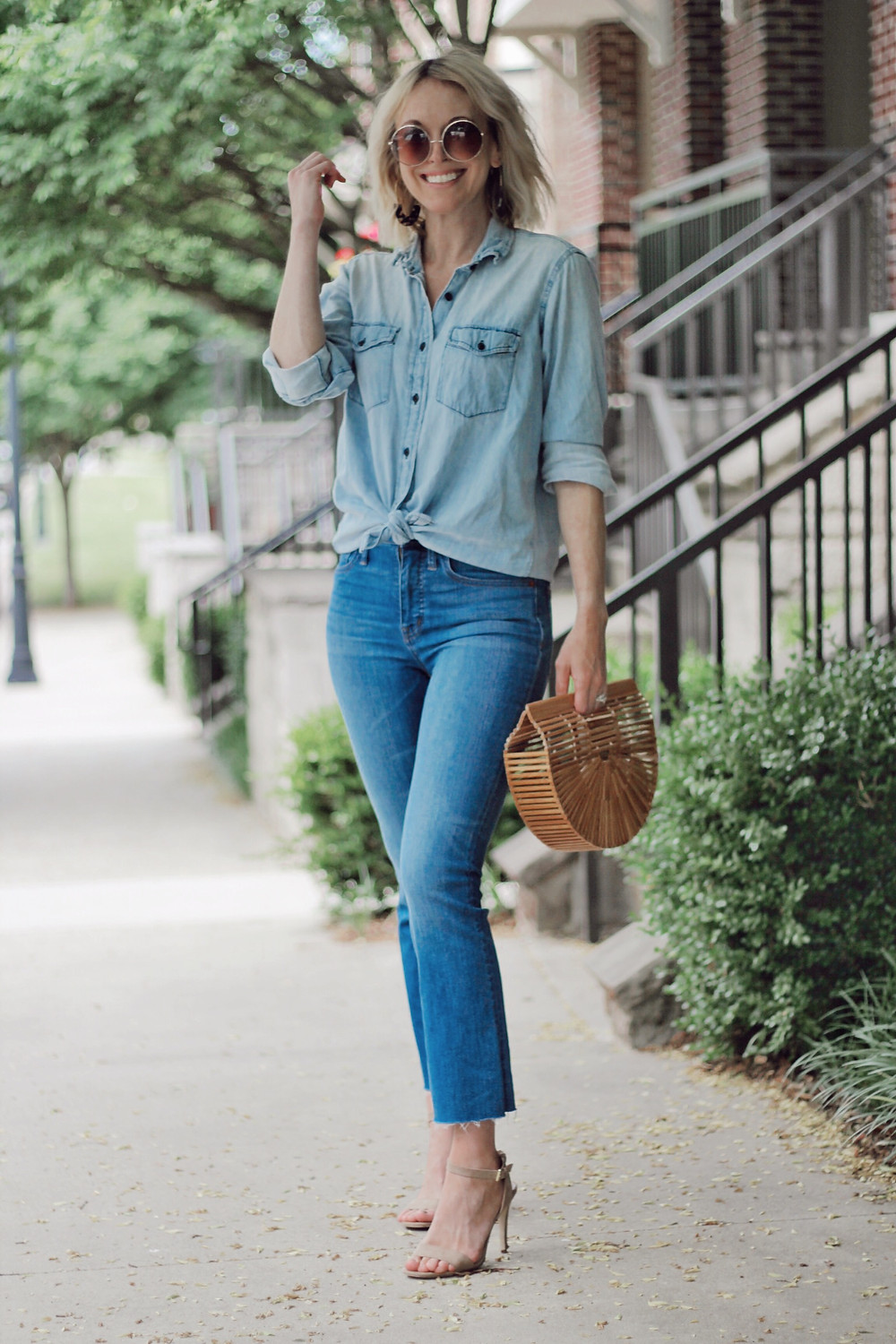 Women wears spring outfit of blue chambray shirt, cropped jeans, wooden bag.