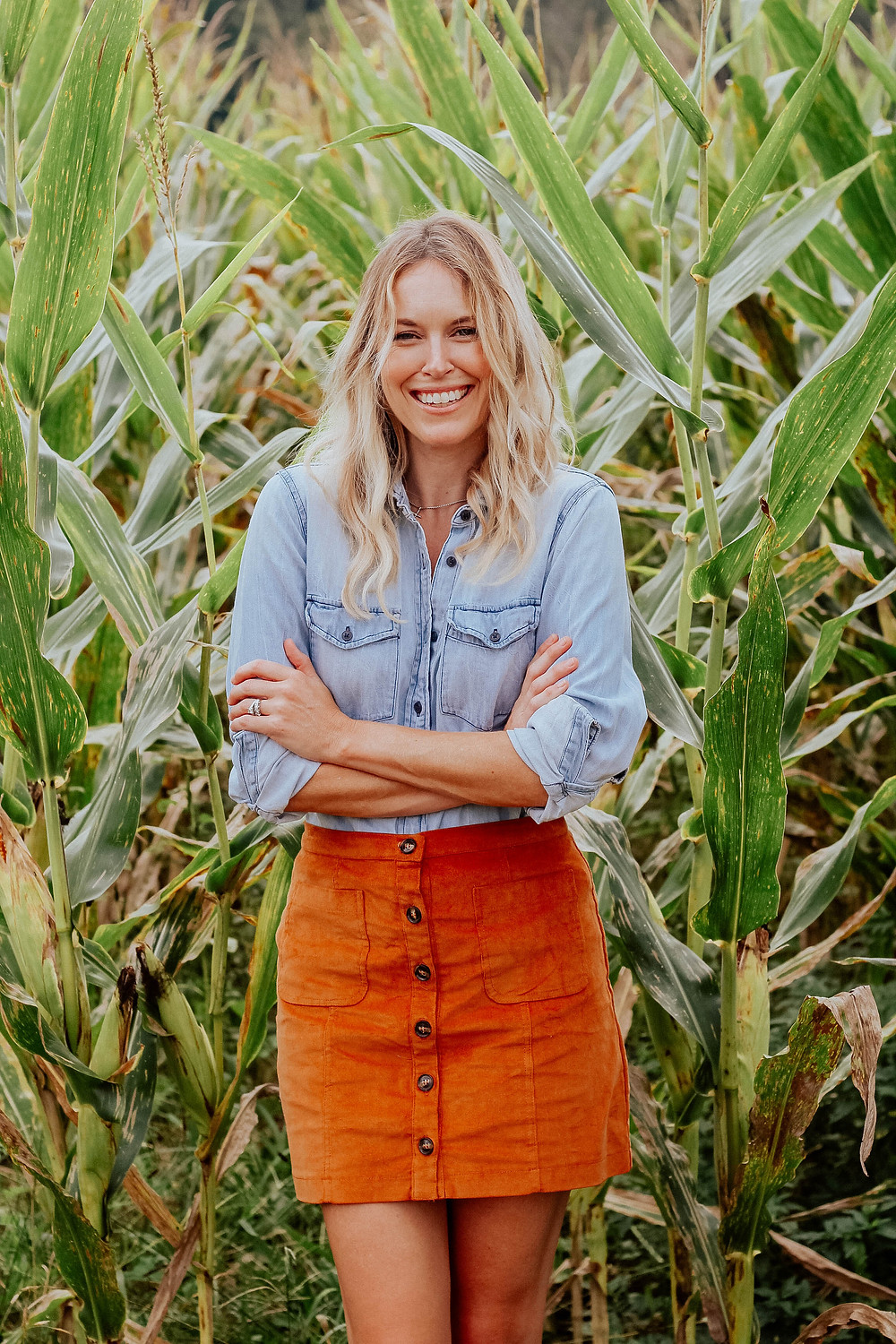Brooke (The Tony Townie) wearing chambray blouse and corduroy skirt walks through corn field.