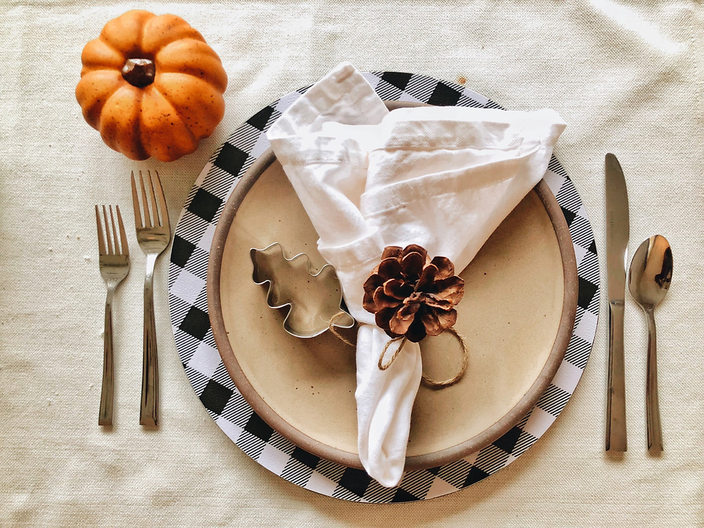 One traditional Thankgiving place setting with a buffalo plaid placemat and pumpkin and pinecone accents.