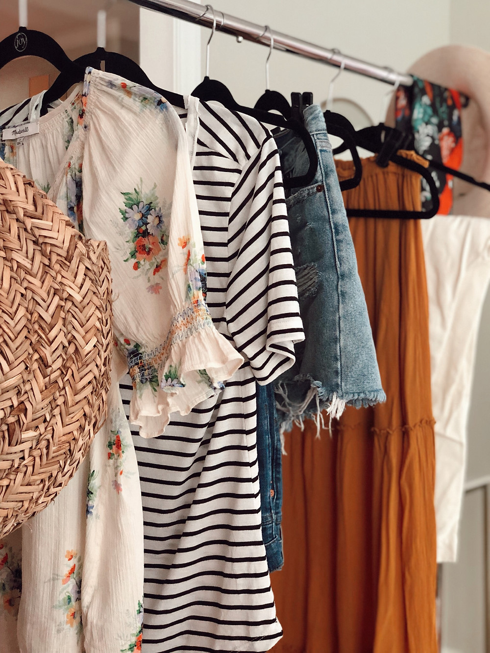 Summer clothing hangs from rolling rack