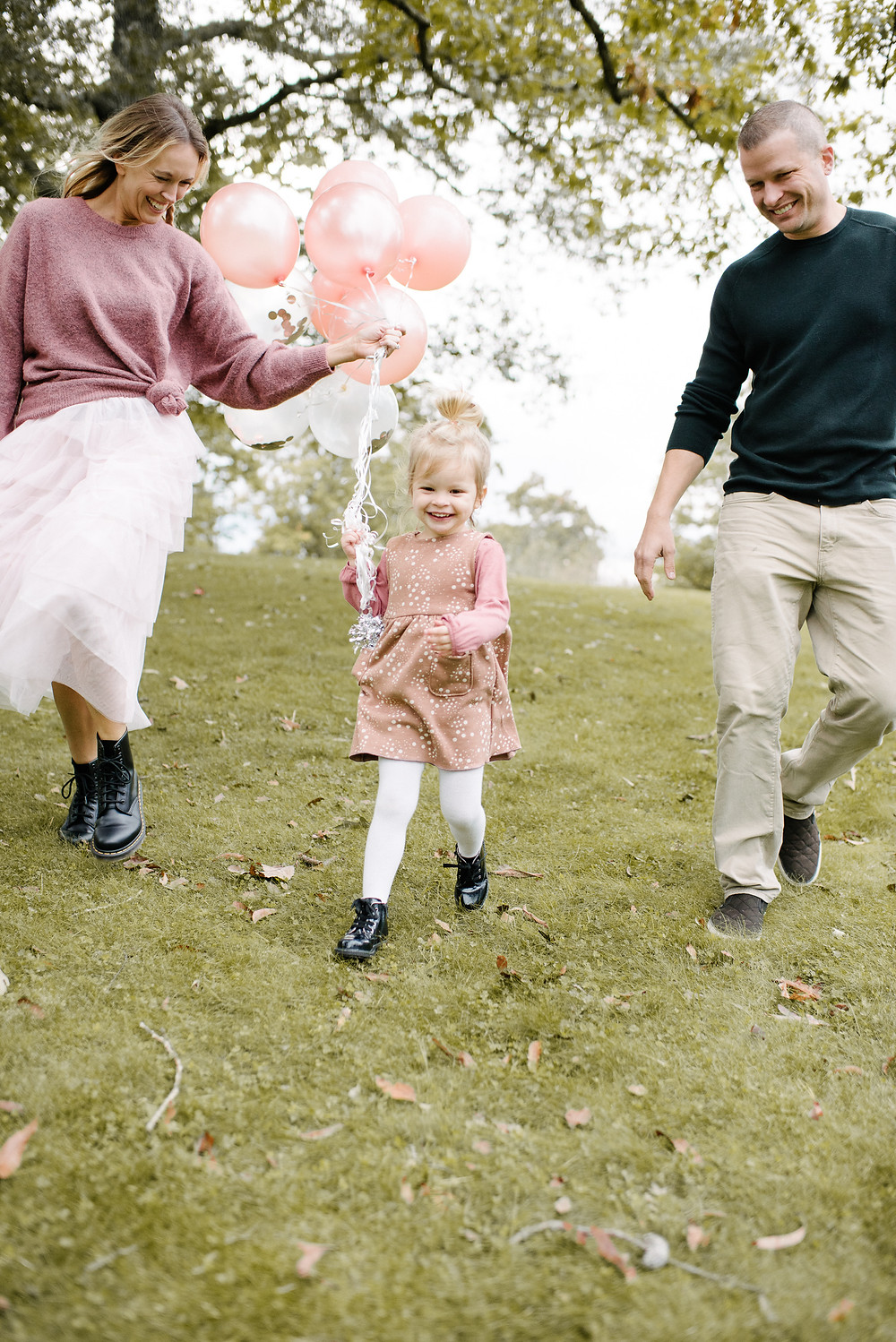 Family of three running with balloons