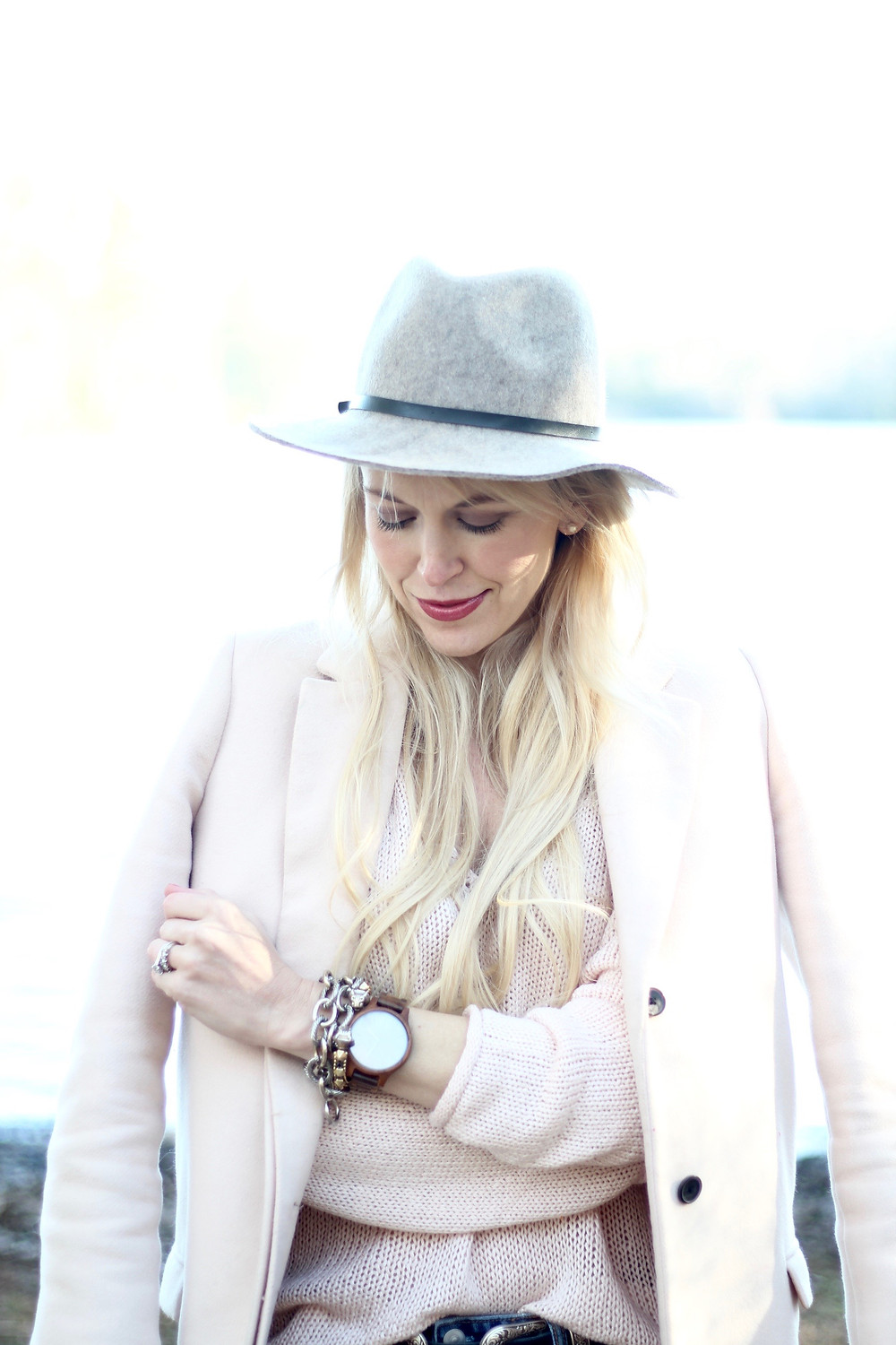 A young mom happily gazes at her JORD Wood Watch, dressed in soft blush pink winter layers.