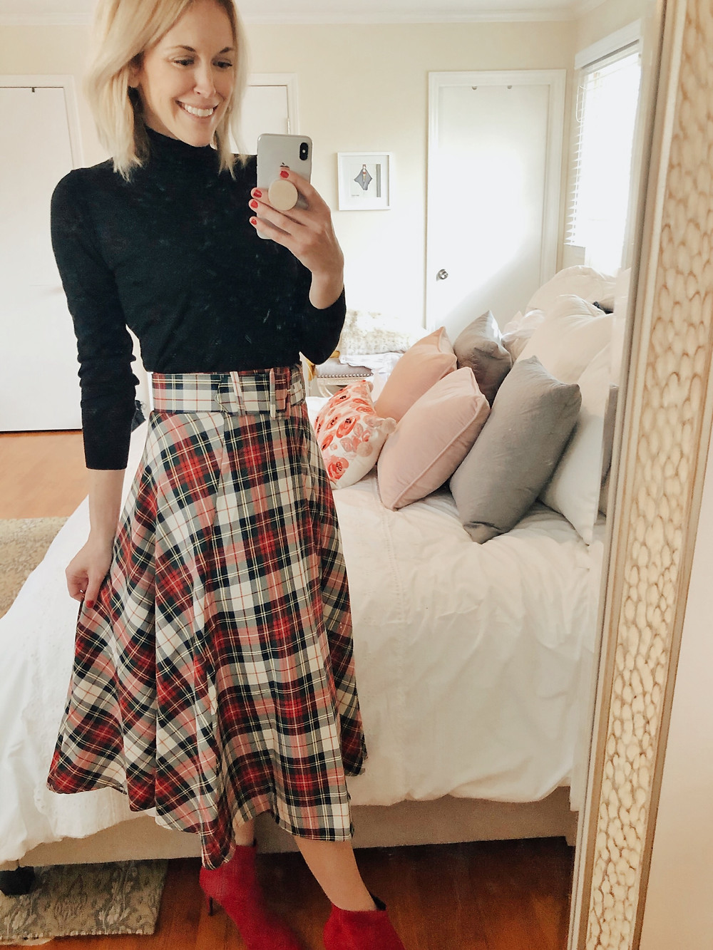 Brooke Williams (The Tony Townie) wears a plaid midi skirt and black turtleneck with red ankle booties.