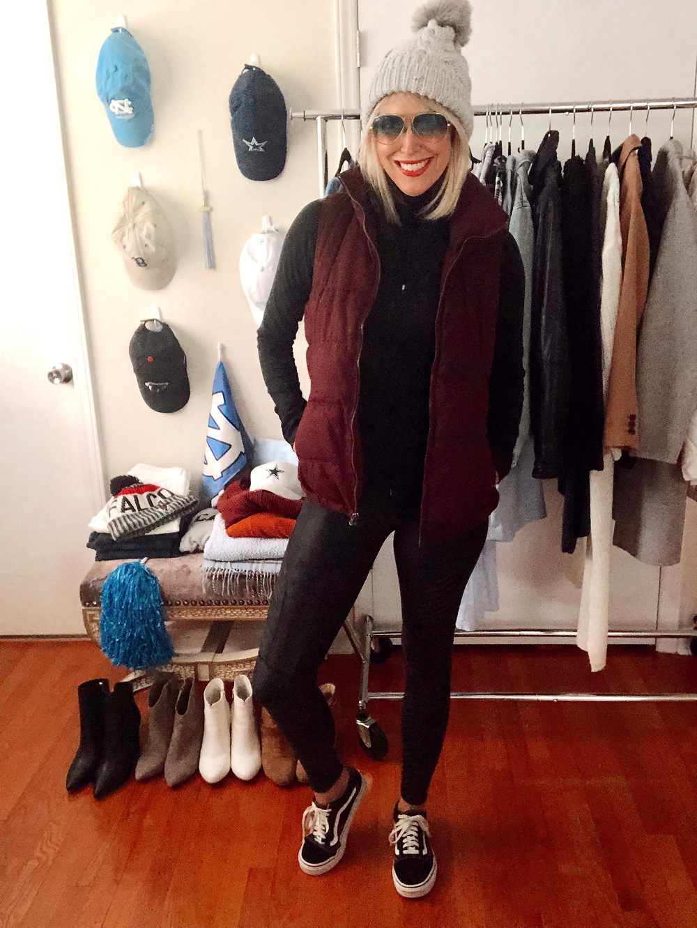 Game day outfit idea for Alabama fans: black turtleneck, black moto leggings, crimson puffer vest, gray knit hat.