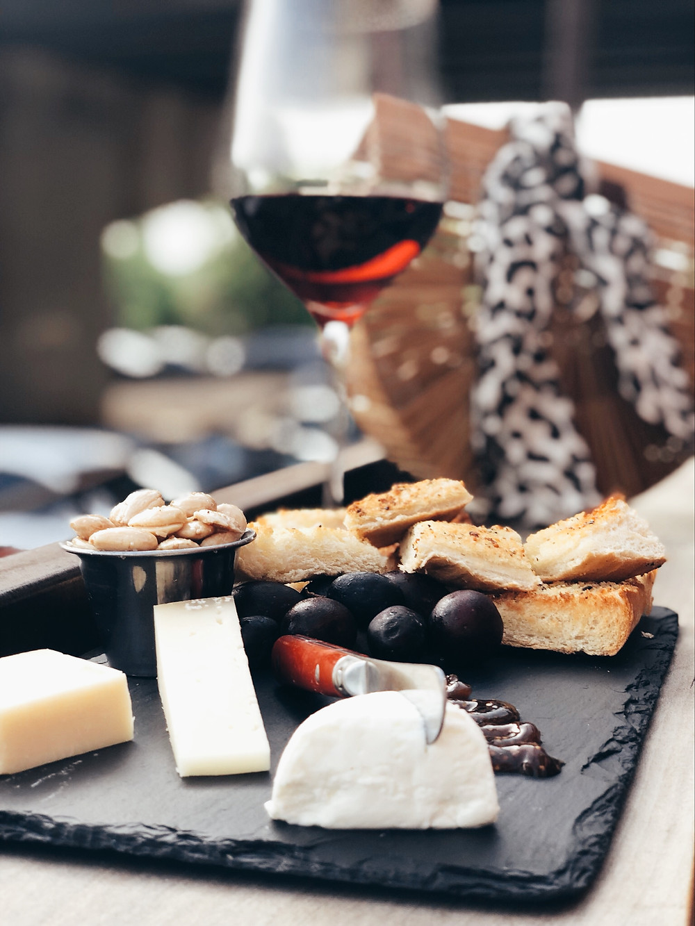 Cheese board with glass of red wine sitting in front of wooden purse with leopard scarf