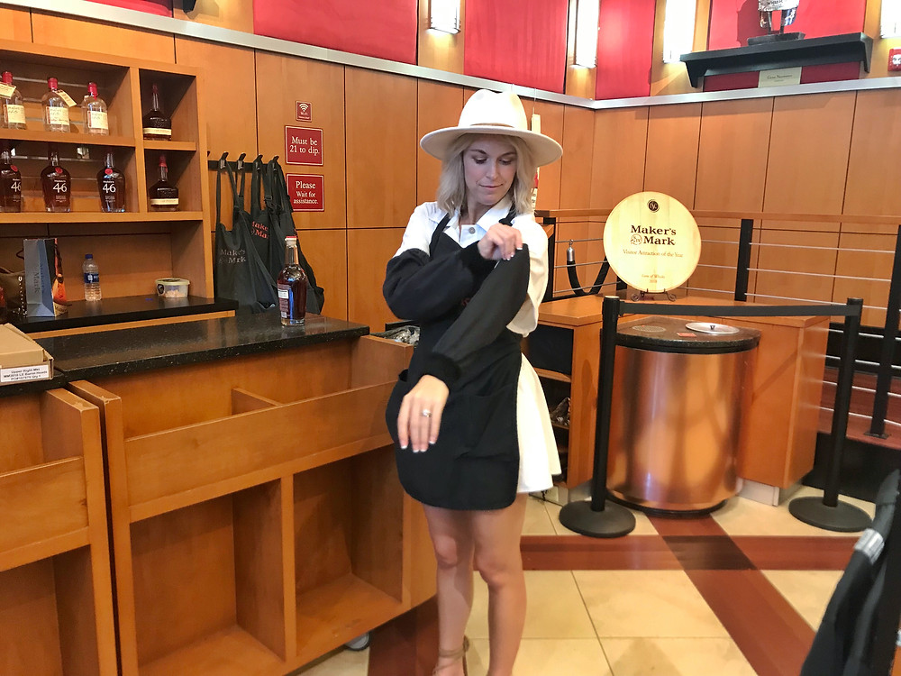 Brooke Williams puts on protective clothing before dipping Maker's Mark bourbon bottle in red wax, Bourbon Trail travel guide, travel blog, best distillery tour