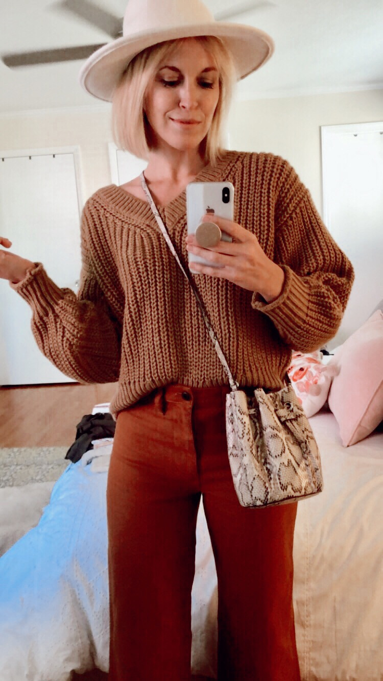 Outfit photo with copper tan sweater, brown pants, white rancher hat, and snake skin bag