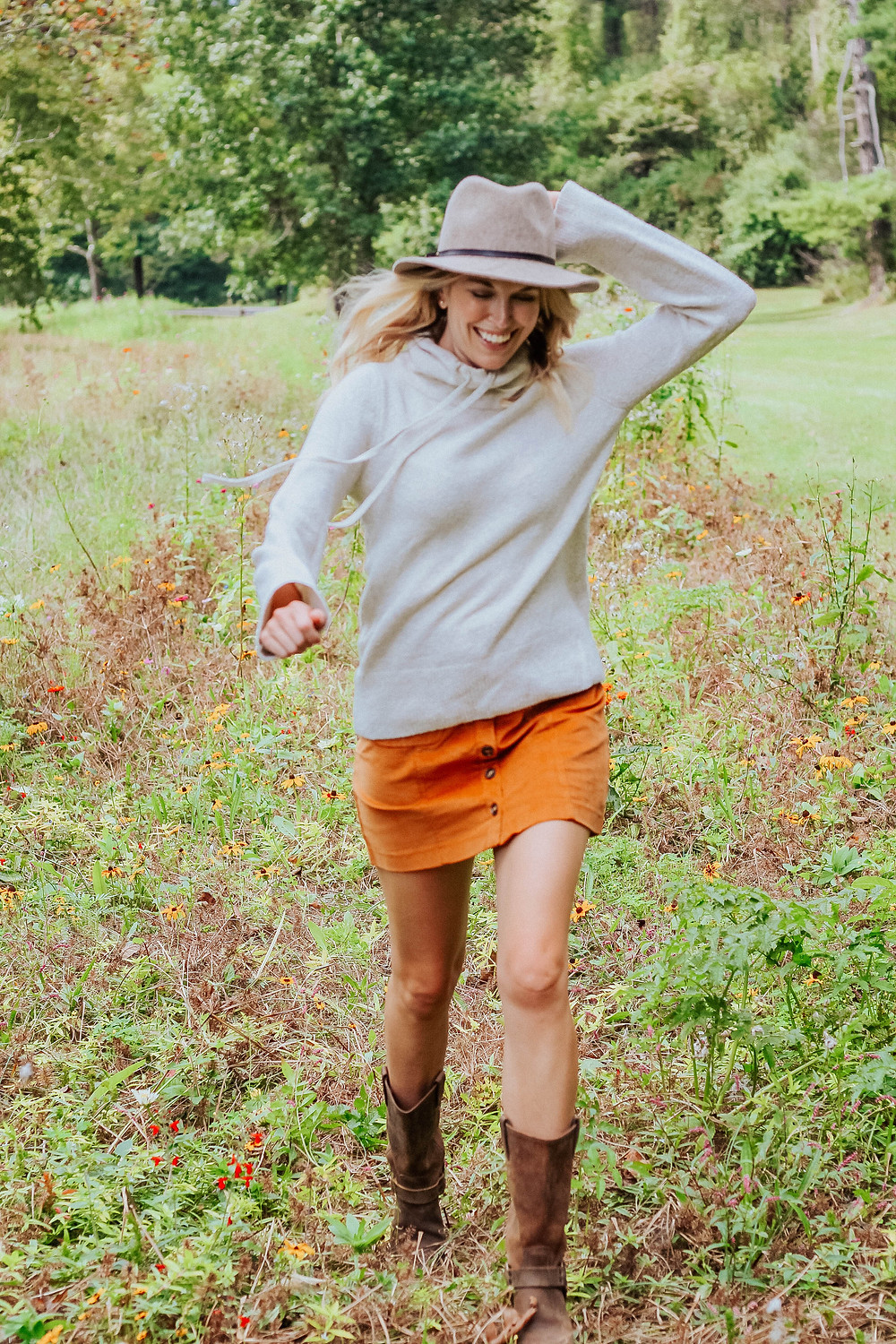Brooke (The Tony Townie) wearing corduroy skirt and sweater runs through field of wildflowers.