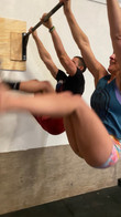 Workout partners doing toes to bar at the best cross training gym in altus