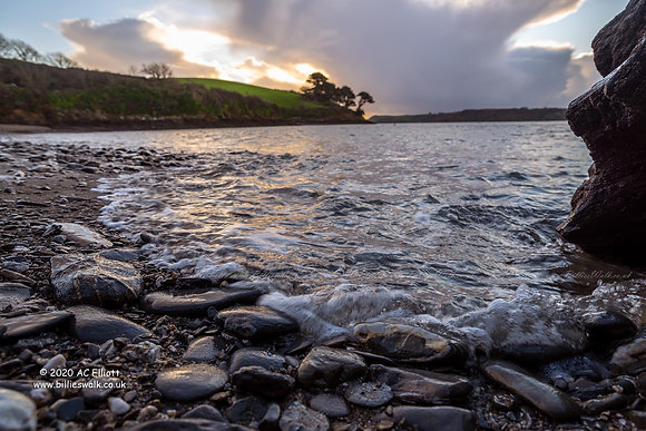 Water rushing over pebbles on Porth Saxon beach photo and fine art print