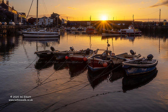 Sunrise behind a row of boats in Mevagissey Inner Harbour photo and fine art print