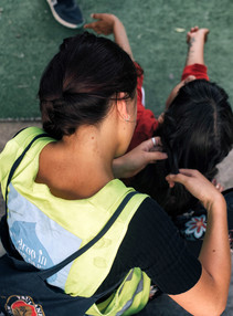 A French volunteer braids a twelve-year-old girl's hair. They discuss living in Turkey