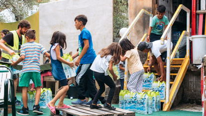 Children help move supplies into storage area. Water to the grounds was cut off intermittently so bottled water had to be brought in, this was enough for two days.