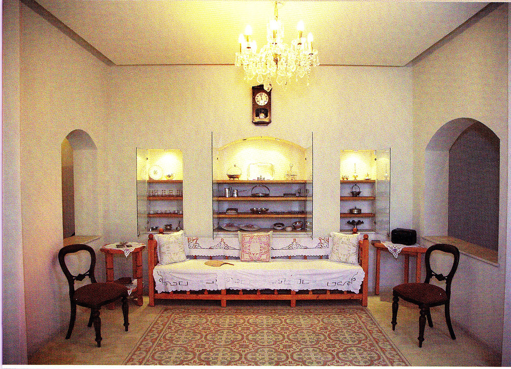 The room is built of white walls with two arched windows on its sides. In the center of the middle wall is an alcove with wooden shelves on which beautiful housewares laid on.  The floor is decorated like a rug of colored ceramic tiles adorned with geometric patterns, which around it the furniture is placed.  The sofa and cushions wrapped in white fabric adorned with lace, and two upholstered wooden chairs and two small refreshment tables are placed on its two sides. A clock hangs over the alcove, and a sumptuous crystal chandelier adorns the ceiling.