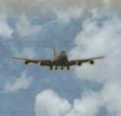 בתוך שמיים כחולים עם עננים לבנים נראה מטוס לפני נחיתה.