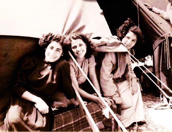 שלוש נערות לבושות בחצאית ארוכה וחולצה, יושבות בפתח אוהל. מעברו השני של הפתח עומד בחור צעיר. כולם מסתכלים על המצלמה ומחייכים.